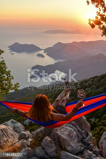 Woman drinking wine in hammock at sunset.