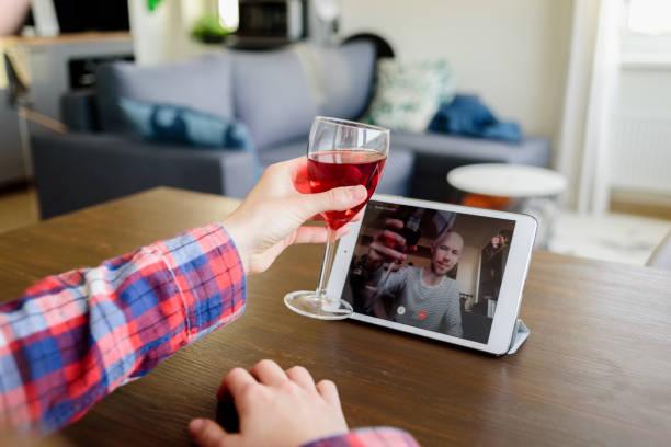 Woman drinking wine online with male friend