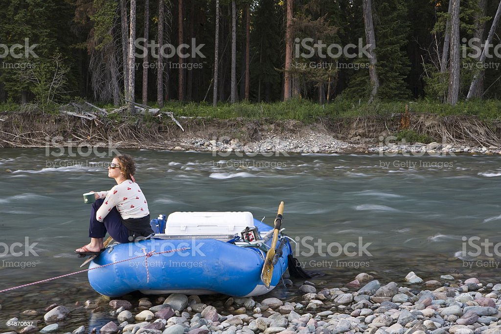 A woman drinks coffee by a river. royalty-free stock photo