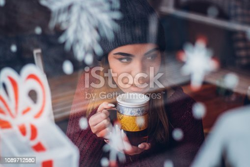 One beautiful young woman with knit hat drinks tea at cafe