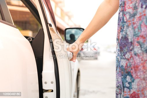 539841066 istock photo woman driver hand open the car door 1059046180