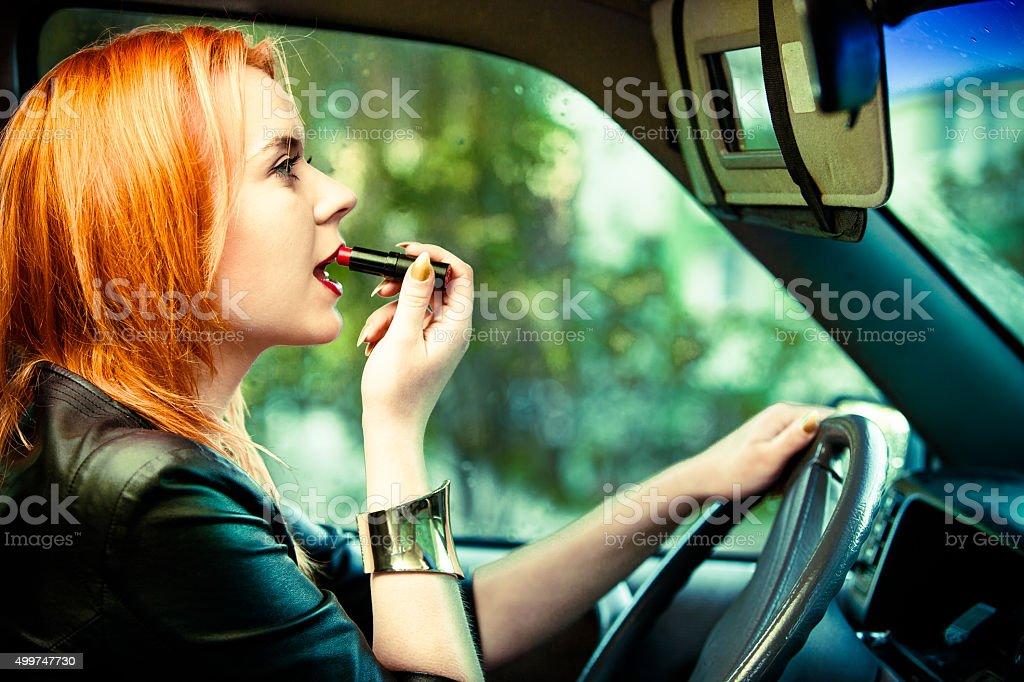 Mulher motorista pintura seus lábios enquanto estiver dirigindo um carro - foto de acervo