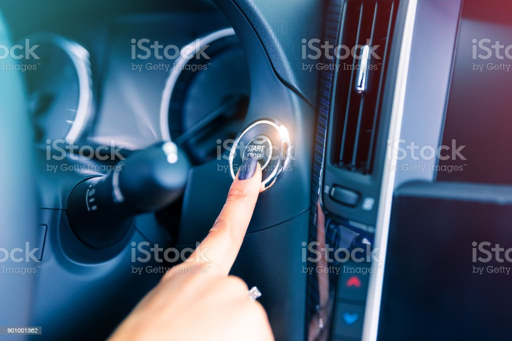 Woman driver pushing a start ignition button in the car stock photo