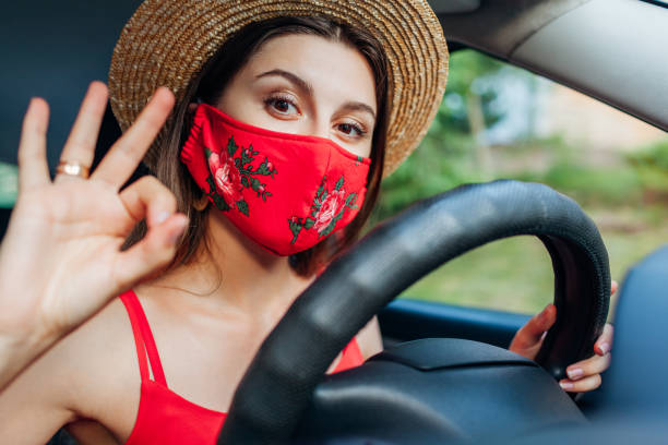 Woman driver sitting in car wearing protective mask during coronavirus pandemic. Girl shows ok cool sign