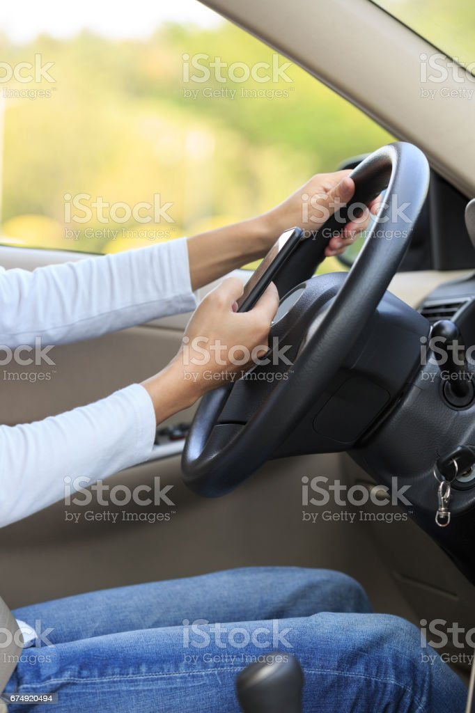 Woman driver use smartphone while driving car royalty-free stock photo