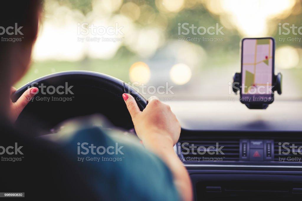 Eine Frau fährt ein Auto bei Sonnenuntergang – Foto