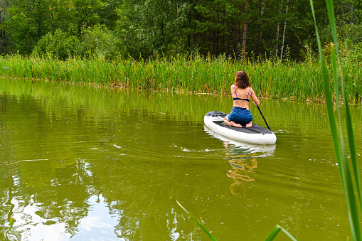 A woman drives on the Sup Board through a narrow canal surrounded by dense grass. Active weekend vacations wild nature outdoor. The woman is sitting on the lap in a jeans.