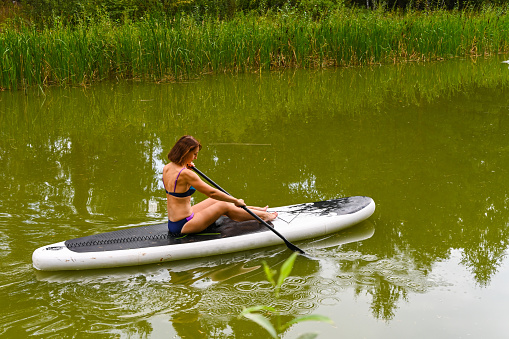 A woman drives on the Sup Board through a narrow canal surrounded by dense grass. Active weekend vacations wild nature outdoor. A woman is sitting with her legs stretched out.