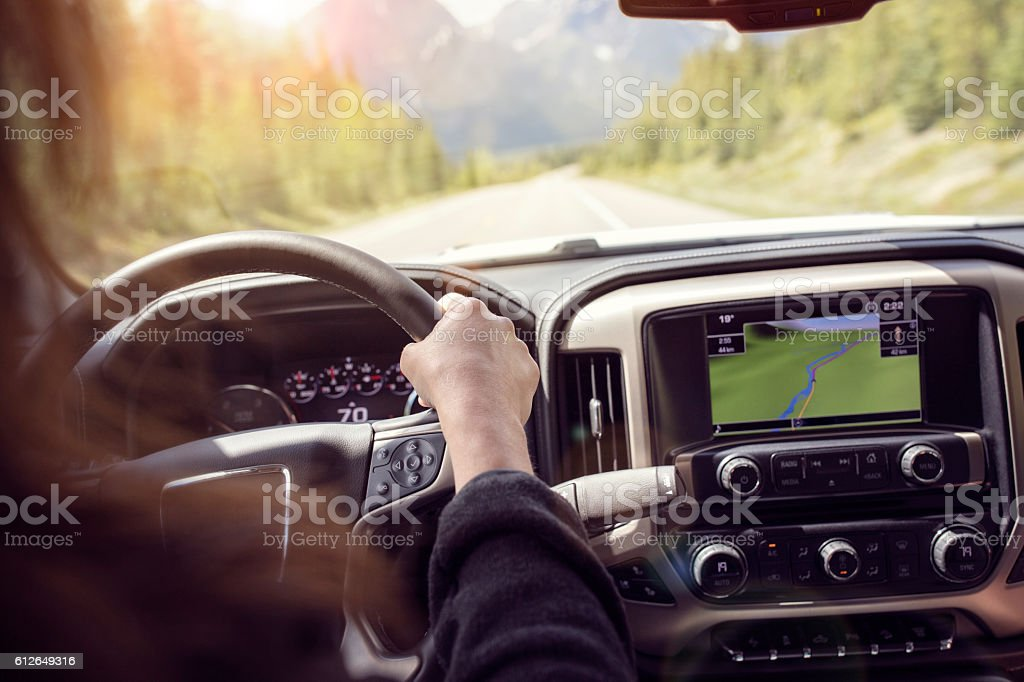 Woman driving a car on a rural road through the mountains stock photo