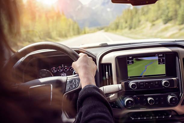 woman driving a car on a rural road through the mountains - sistema de posicionamiento global fotografías e imágenes de stock