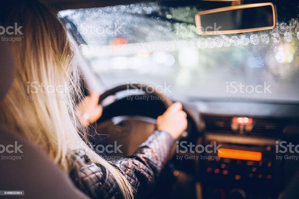 Woman Driving a Car on rainy night stock photo