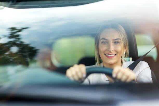 mujer conducir un coche - conducir fotografías e imágenes de stock
