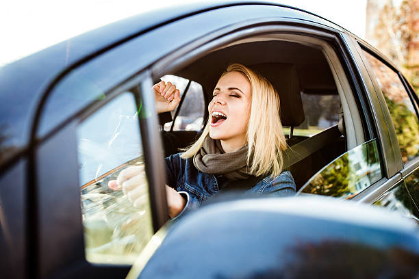 Woman driving a car Beautiful young blond woman driving a car singing stock pictures, royalty-free photos & images