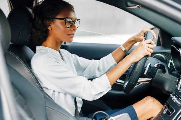 Woman driving a car. Side view of a female driver wearing glasses and looking away. stock photo