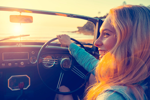 Woman driving a convertible at the beach. She is happy and smiling.  It is sunset or sunrise. With the ocean in the background. Can be flipped for left hand drive car.