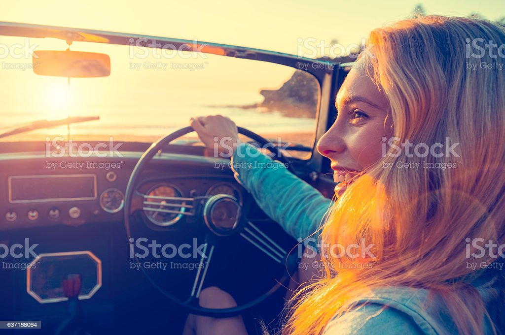 Woman driving a convertible at the beach. stock photo