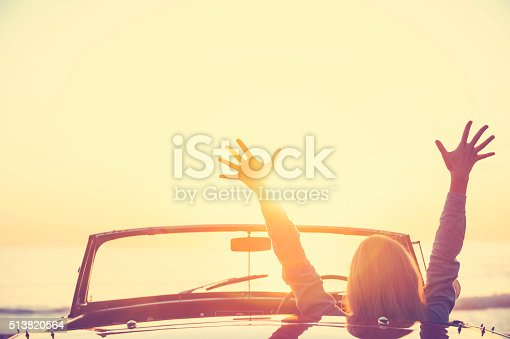 istock Woman driving a convertible car at the beach. 513820564