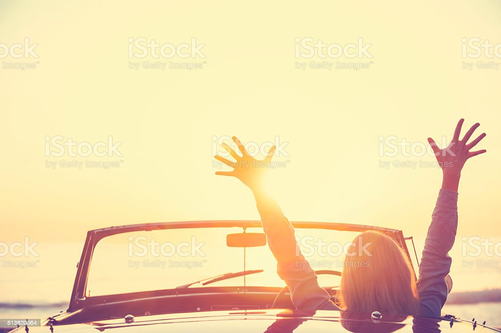Woman driving a convertible car at the beach. stock photo