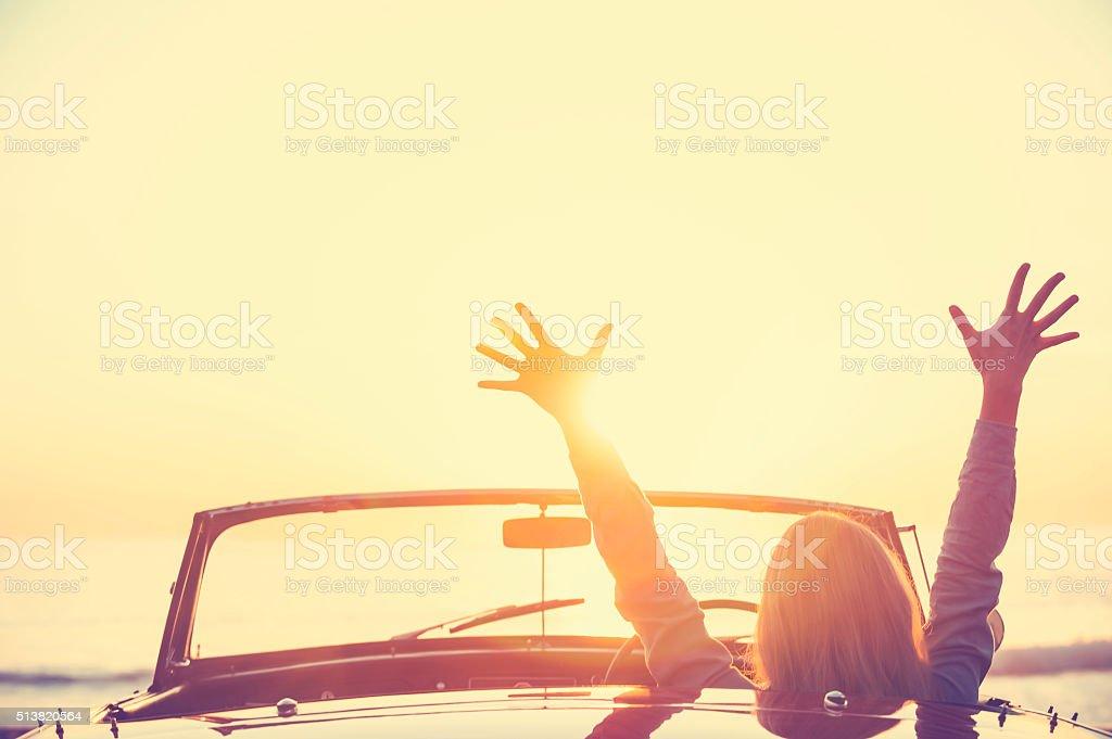 Mulher dirigindo carro conversível na praia. - foto de acervo