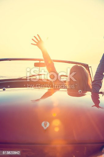 istock Woman driving a convertible car at the beach. 513820942