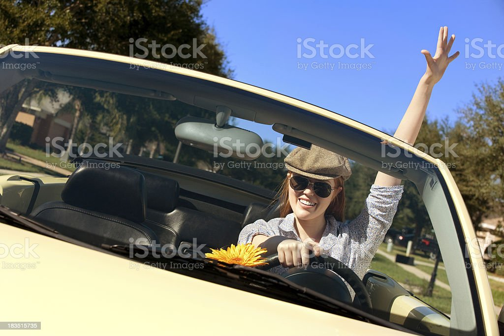 A woman driving a convertible with one arm in the air. stock photo