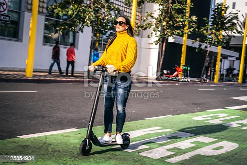 A woman in casual clothes driving an electric scooter in a scooter & bike lane downtown.