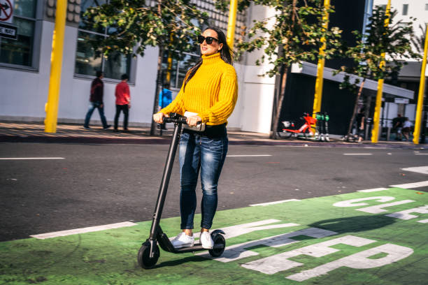 a woman driving an electric scooter on a scooter & bike lane in the city downtown - electric push scooter stock photos and pictures
