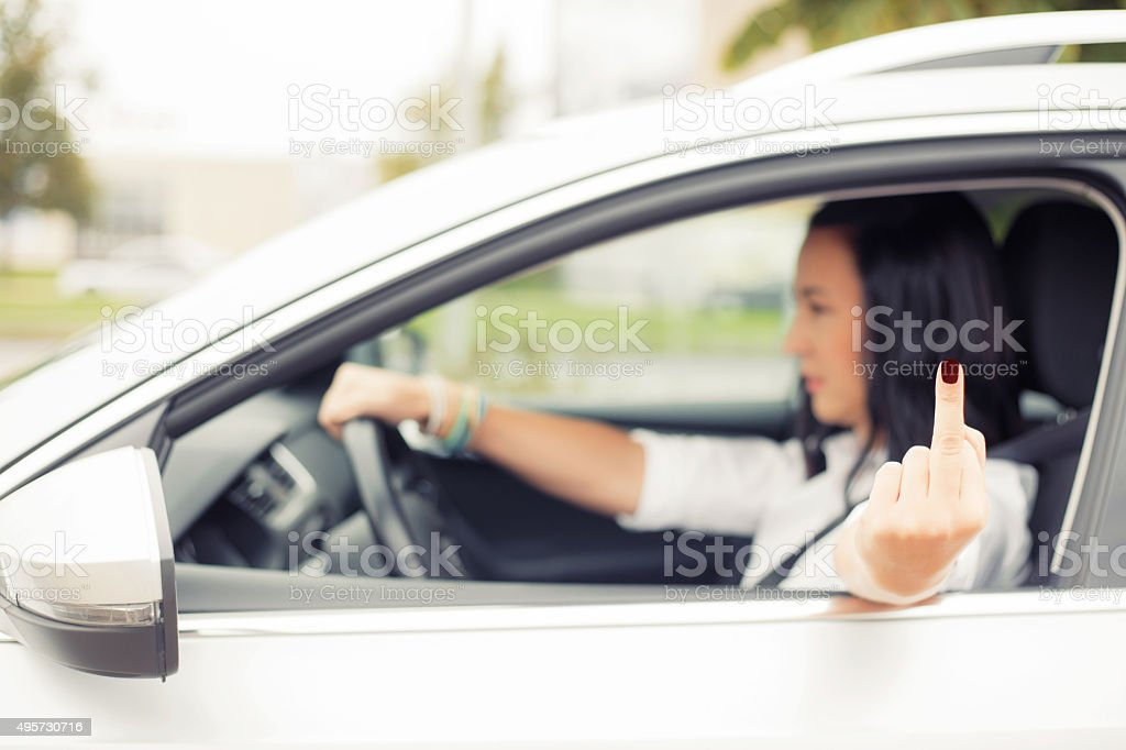 Woman driving and flipping people off with middle finger stock photo