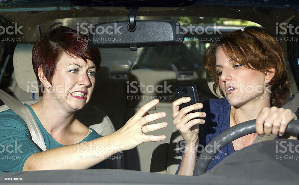 Woman driving and looking at a phone while other argues stock photo