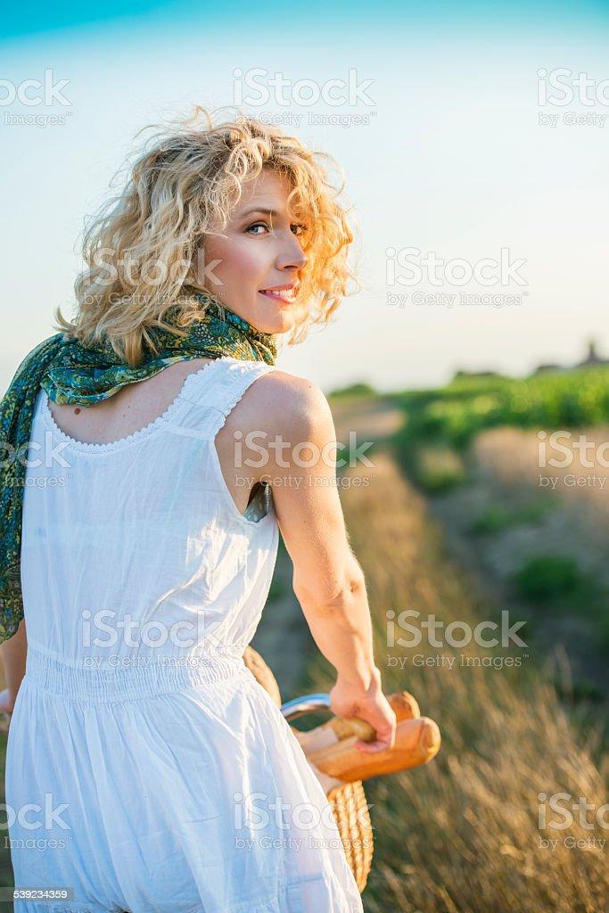 Mulher de bicicleta em campo de trigo integral foto royalty-free
