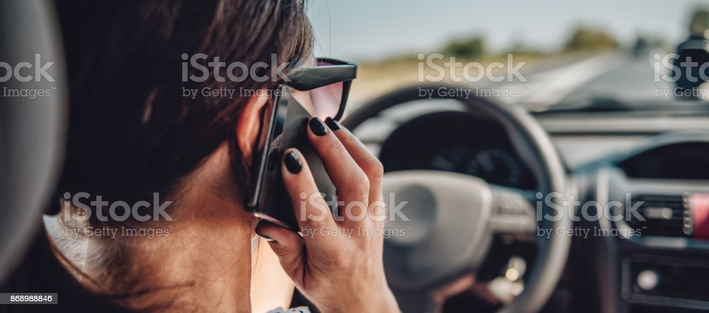 Woman driving car and talking on smart phone stock photo