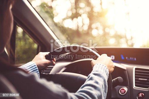 Woman driving car at sunny.