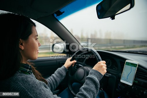 istock woman driving car by highway in foggy time 866962398