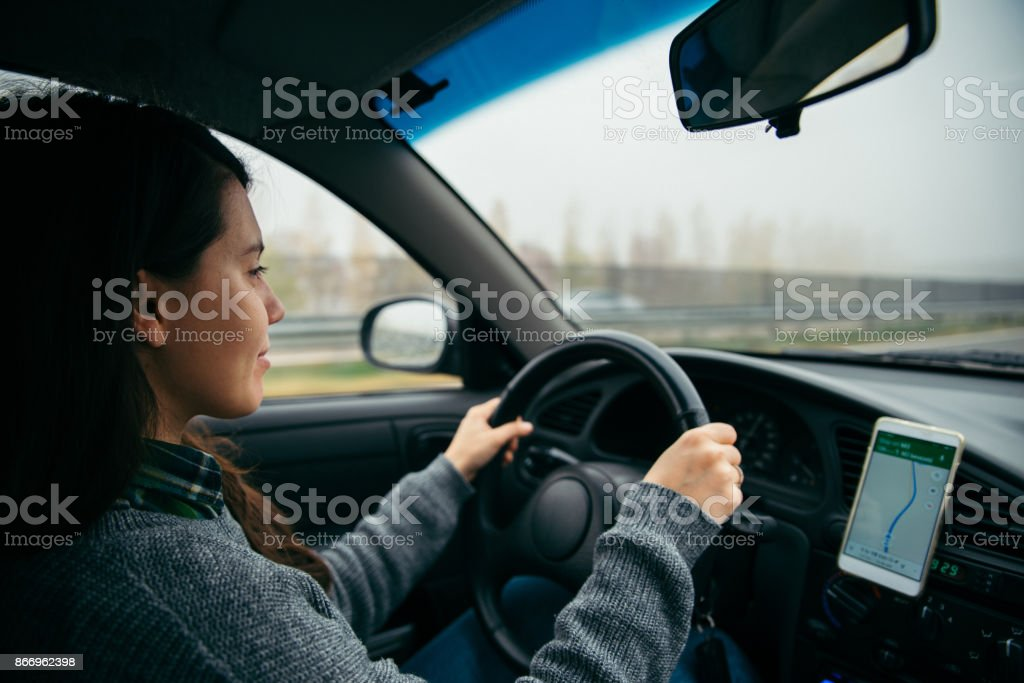 woman driving car by highway in foggy time stock photo