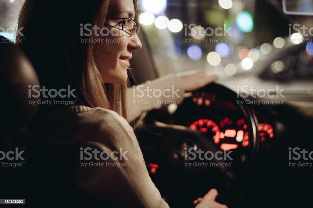 Mujer de conducir coches por la noche en la ciudad - Foto de stock de 20 a 29 años libre de derechos