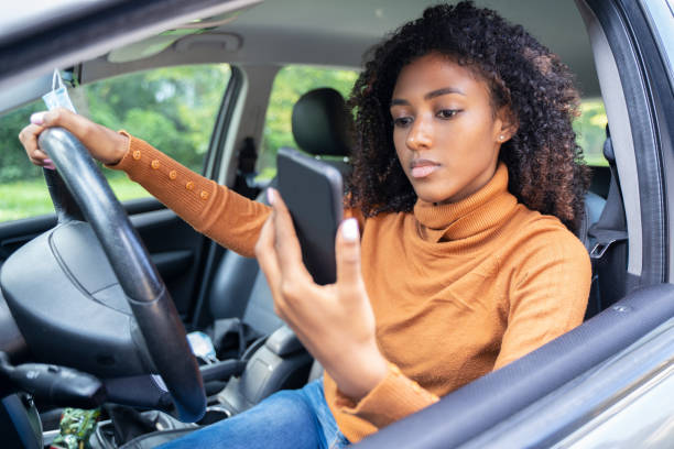 Woman driving car distracted by her mobile phone stock photo