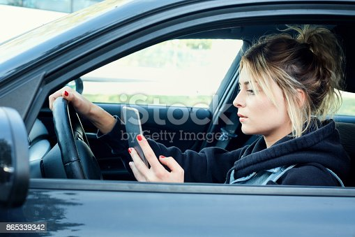 istock Woman driving car distracted by her mobile phone 865339342