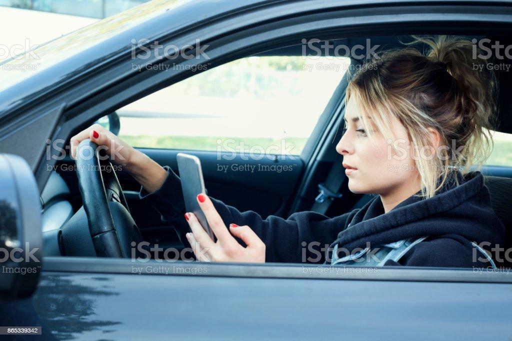 Mulher dirigindo o carro distraído pelo seu telefone móvel - foto de acervo
