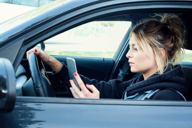 woman driving car distracted by her mobile phone - text messaging stock photos and pictures