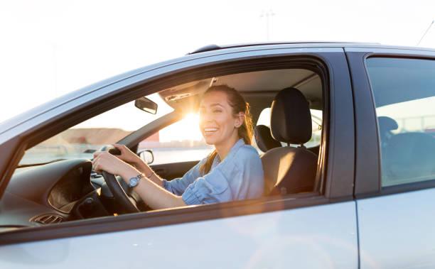 Frau fährt Auto im Sonnenuntergang – Foto