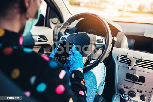 Middle age female driver sitting in car and disinfect her smartphone with alcohol and paper tissue. She is wearing protective mask to protect herself from dangerous flu, virus or allergen. Coronavirus or seasonal allergy concept.
