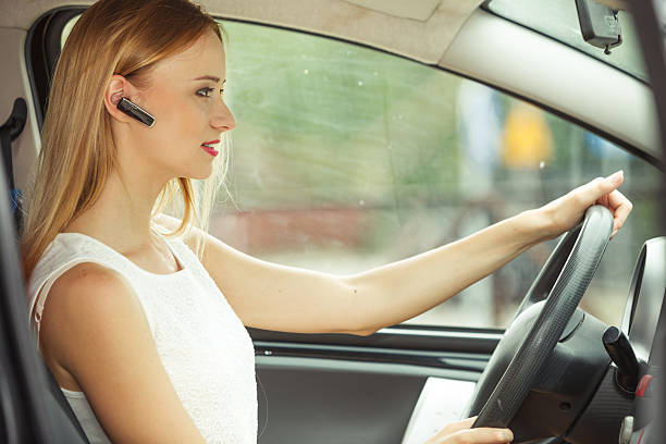 woman driving car with headset Transport and safety concept. Young blonde woman driving car using her mobile phone and headset, side view bluetooth stock pictures, royalty-free photos & images