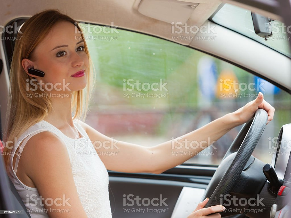 woman driving car with headset stock photo