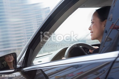 620402800istockphoto Woman driving car with reflections of flags on door 618946058