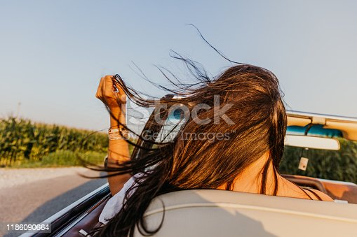 Rear view shot of a brunette driving a convertible car on a country road