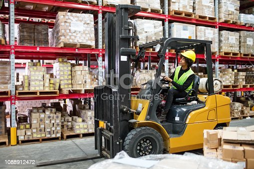 Woman driving forklift carefully through aisle in warehouse. Female worker driving forklift in warehouse.