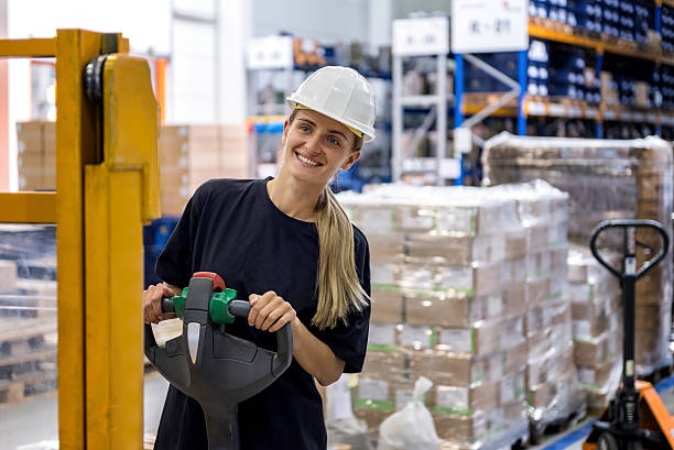 Woman driving pallet truck Smiling busy woman drives pallet truck in warehouse of huge factory. She is wearing protective workwear, white hard helmet and black t-shirt. She is delivering shipment. pallet jack stock pictures, royalty-free photos & images