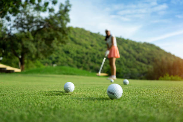 Woman driving practice golf or trainer at golf course on the fairway at sunset stock photo