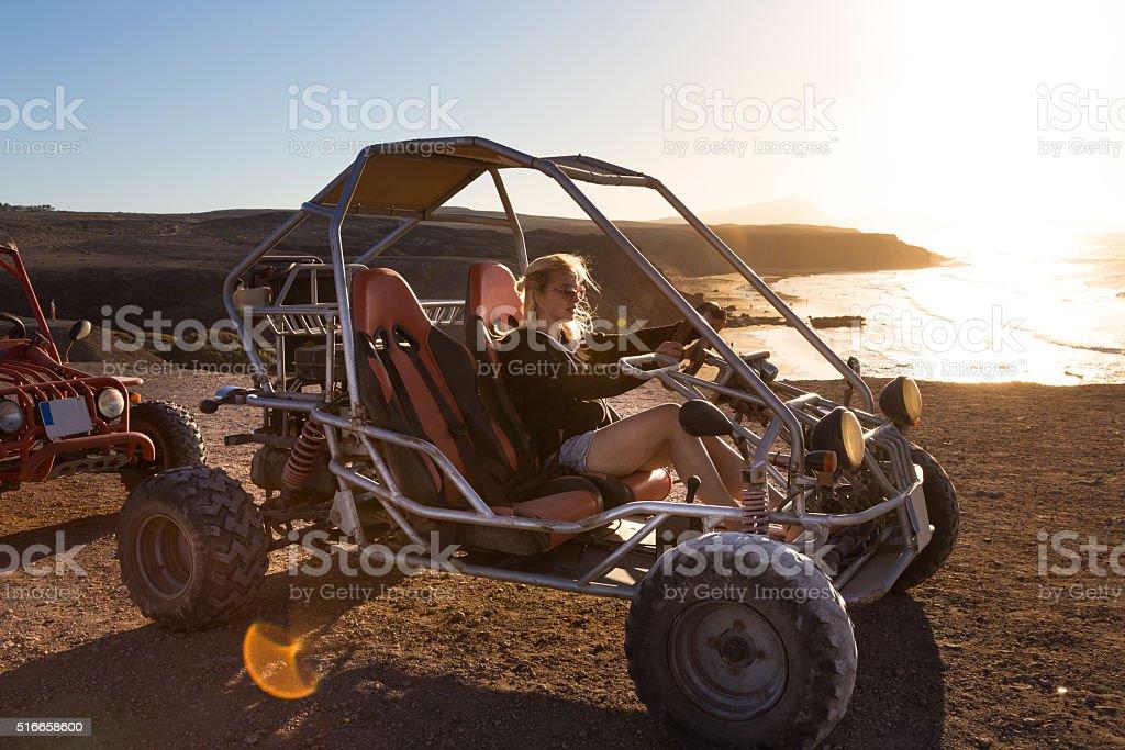 Femme en quad dans le coucher du soleil. - Photo