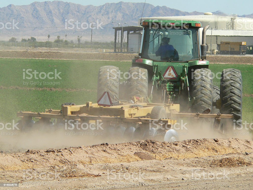Woman driving tractor plowing alfalfa field royalty-free stock photo